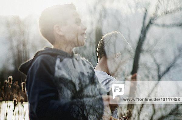 Spiegelung von Jungen und kahlen Bäumen auf Glas