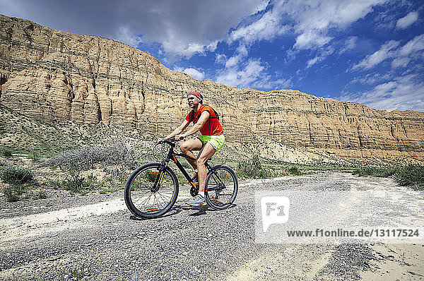 Side view of hiker riding bicycle on desert against rock formations