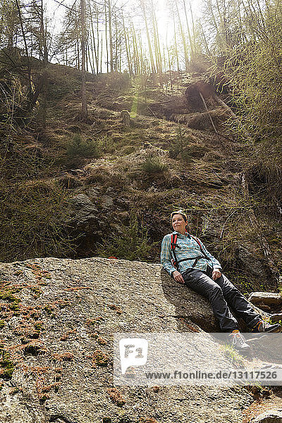 Wanderin entspannt sich am Fels