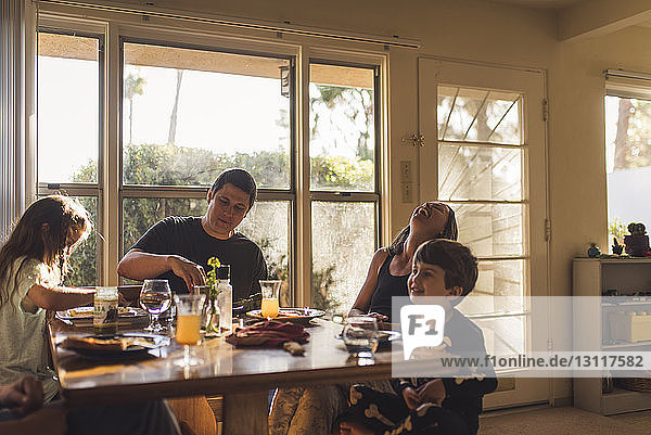Happy family having breakfast at dining table