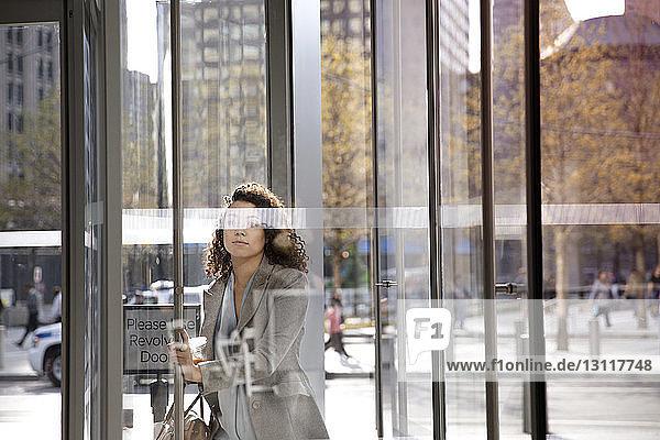 Geschäftsfrau öffnet Karusselltür beim Betreten eines modernen Gebäudes