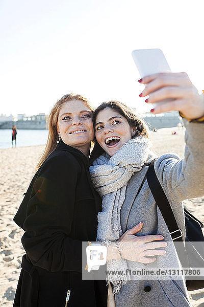 Fröhliche Mutter und Tochter beim Selfie mit Smartphone am Strand