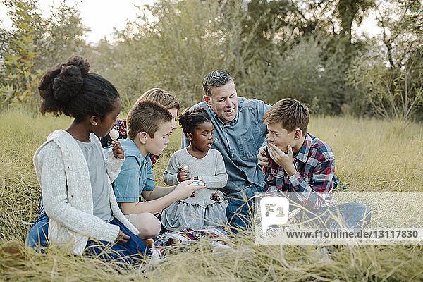 Eltern sehen Kindern beim Essen zu  während sie auf dem Feld im Park sitzen