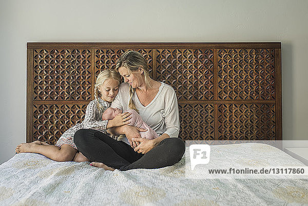 Mother and daughter looking at newborn baby while sitting on bed