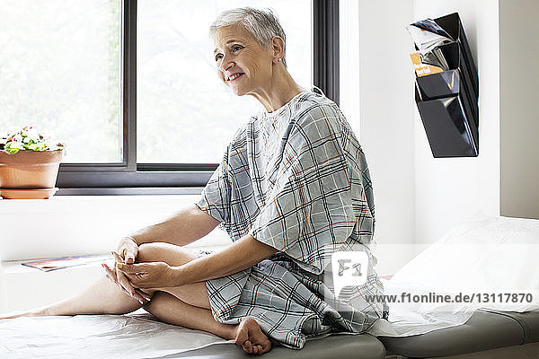 Happy thoughtful woman looking away while sitting on bed at clinic