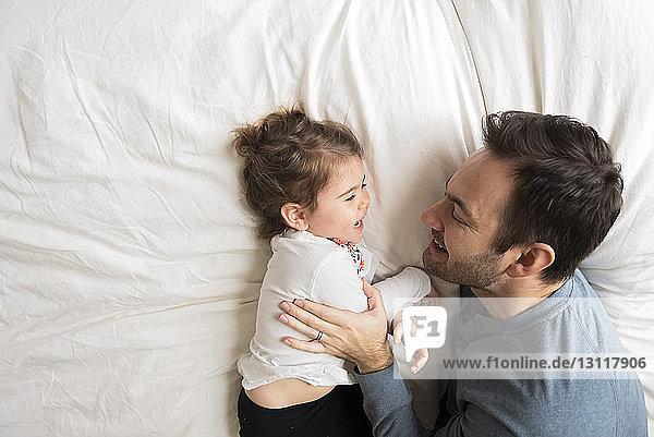 Draufsicht auf fröhliche Vater und Tochter  die zu Hause auf dem Bett liegen