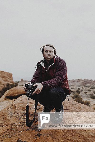 Porträt eines Mannes  der eine Kamera hält  während er auf einem Felsen gegen den Himmel kauert