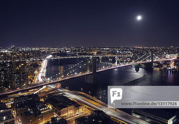 Hochwinkelansicht der beleuchteten Stadtlandschaft und der Brooklyn Bridge bei Nacht