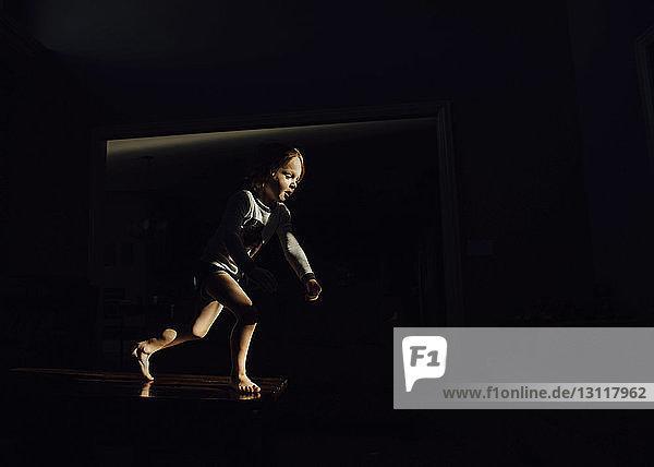 Boy running in dark room at home