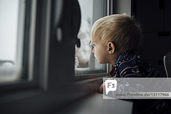 Side view of baby boy looking through window while standing at home