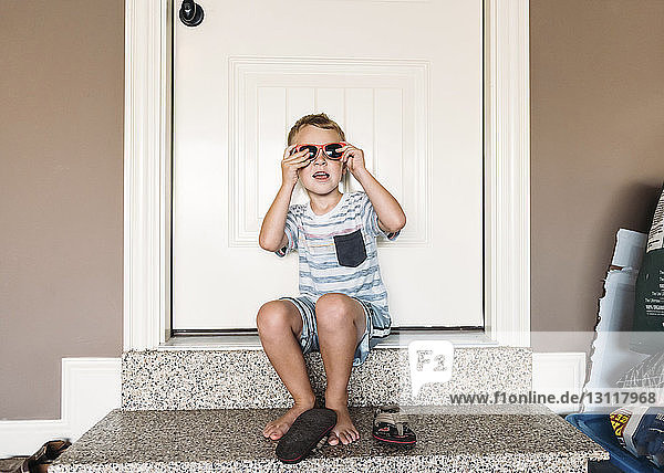 Boy wearing sunglasses while sitting on doorway