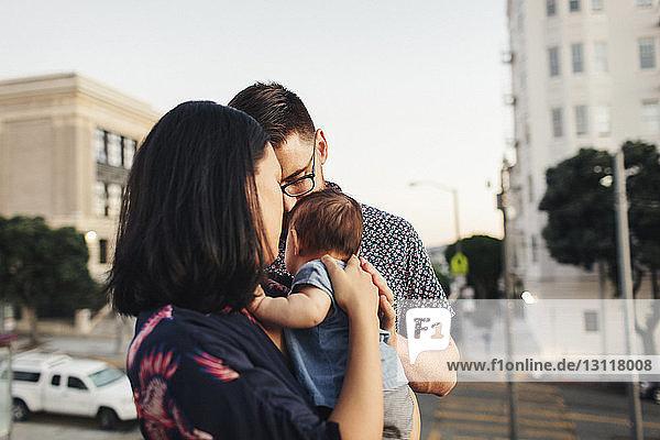 Eltern mit Tochter stehen auf Stadtstraße gegen Himmel