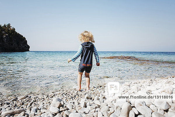 Rear view of girl standing on shore against clear sky at Bruce Peninsula National Park