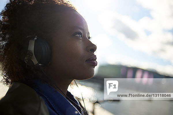 Close-up of thoughtful woman listening music