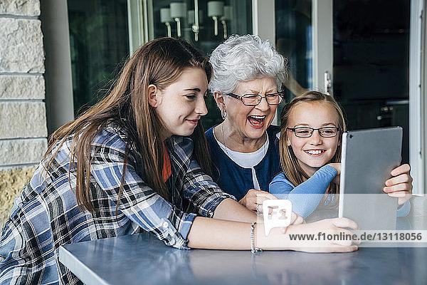Glückliche Enkeltöchter und Großmutter mit Tablet-Computer auf der Veranda