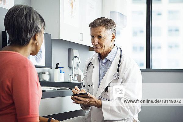 Männlicher Arzt schreibt in Notizblock  während er mit Patientin in der Klinik diskutiert