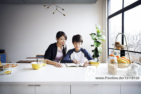Mother looking at son studying on table at home