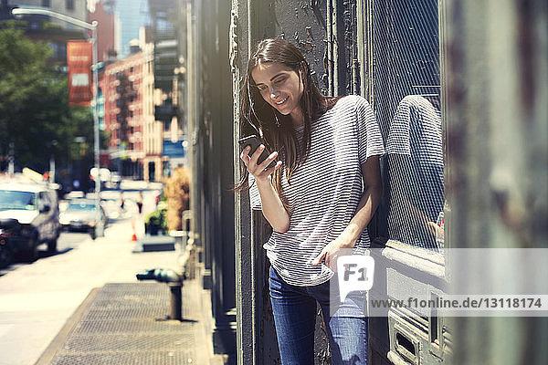 Lächelnde Frau benutzt Smartphone an einem sonnigen Tag