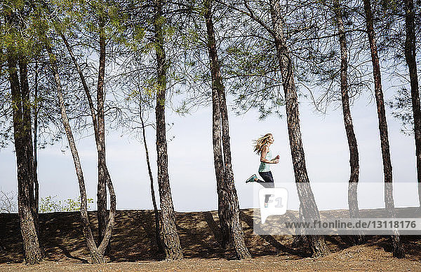 Side view of woman running on field amidst trees