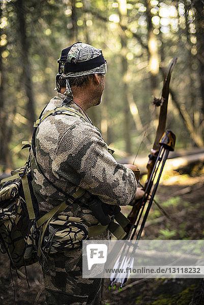 Jäger mit Pfeil und Bogen im Wald stehend