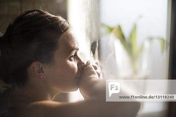 Nahaufnahme einer schwangeren Frau in den Wehen zu Hause am Fenster