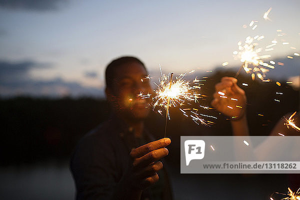 Friends holding sparklers at night