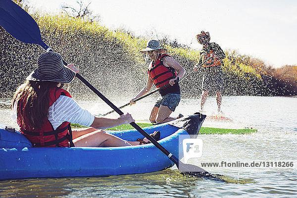 Freunde spritzen Wasser auf eine Frau,  die in einem aufblasbaren Kajak sitzt,  während sie auf dem See paddeln