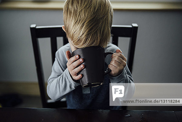 Schrägaufnahme eines Jungen  der zu Hause auf einem Stuhl sitzt und trinkt