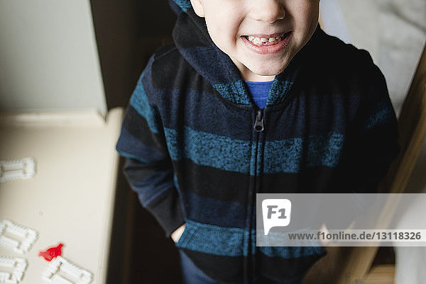 Midsection of boy with hands in pockets standing at home