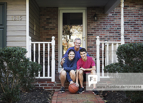 Portrait of smiling grandfather with grandchildren sitting on front stoop