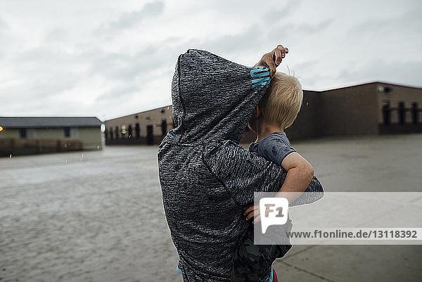 Rückansicht der Schwester  die den Bruder trägt  während sie auf der Straße vor bewölktem Himmel steht