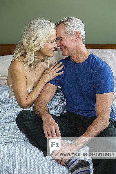 Paarromantik zu Hause im Bett sitzend