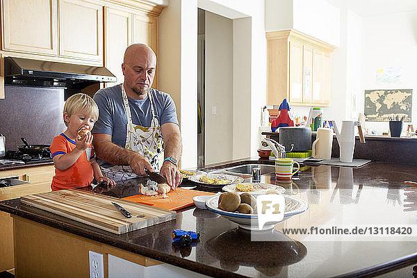 Junge isst Apfel  während der Vater an der Küchentheke Kartoffeln schneidet