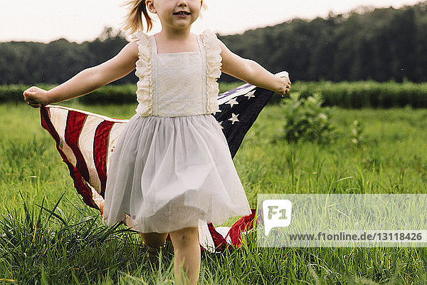 Midsection of girl holding American flag while walking on grassy field