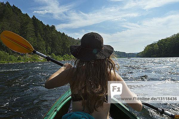 Rückansicht einer Frau Ruderboot im Fluss