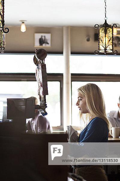 Seitenansicht einer Frau  die von Kunden im Cafe an der Theke steht