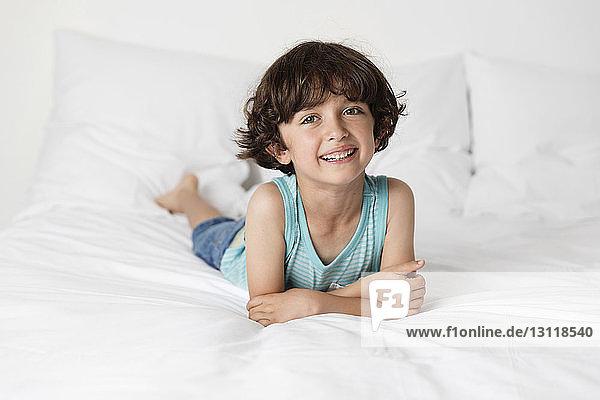Porträt eines süßen  glücklichen Jungen  der sich zu Hause auf dem Bett ausruht
