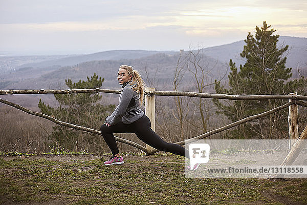 Woman exercising on field against cloudy sky at Fruska Gora National Park