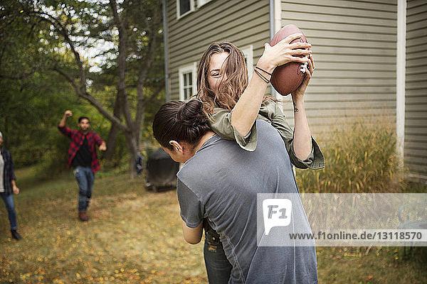 Paar spielt mit Freunden auf dem Feld Fussball