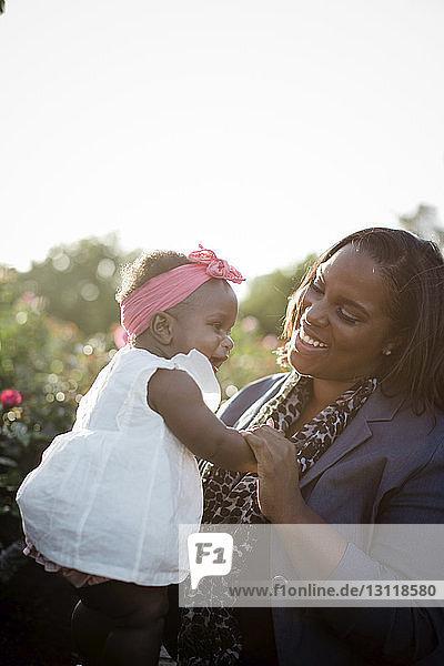 Fröhliche Mutter spielt mit ihrer Tochter  während sie im Park bei Pflanzen vor dem klaren Himmel sitzt
