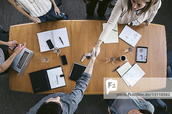 High angle view of business people shaking hands in board room