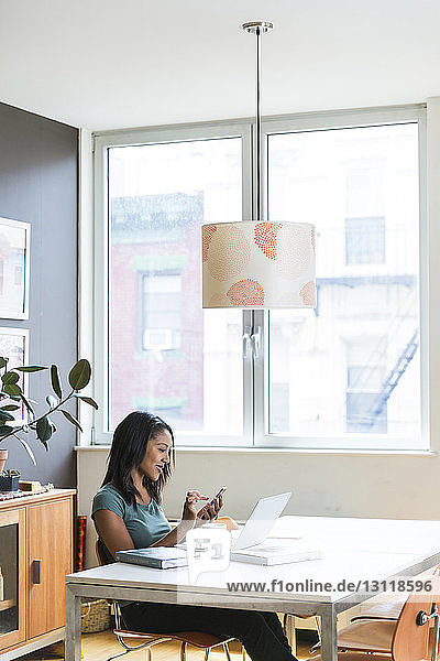 Woman using smart phone while working at home office