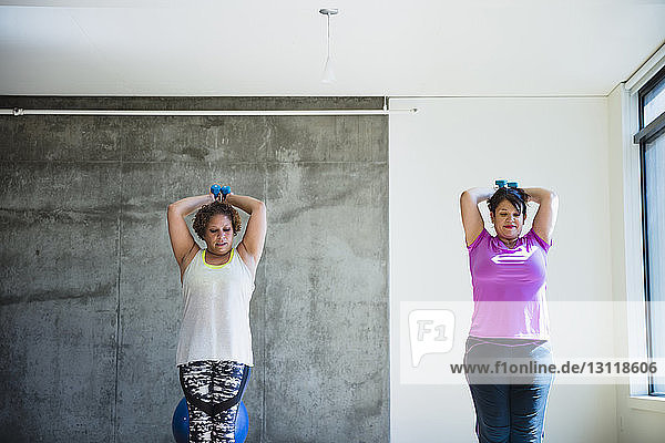 Confident friends using dumbbells while exercising against wall in yoga studio