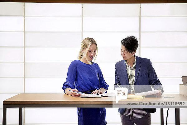 Weibliche Kollegen diskutieren  während sie im Büro am Tisch stehen