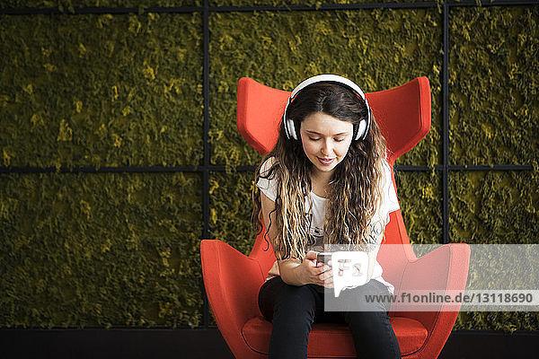 Frau hört Musik  während sie zu Hause auf einem Sessel an der Wand sitzt