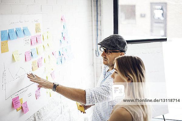Geschäftsmann erklärt seiner Kollegin im Kreativbüro Strategie
