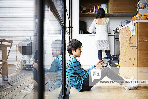 Boy sitting on floor and using digital tablet while mother standing in kitchen