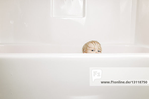 Portrait of boy peeking while sitting in bathtub