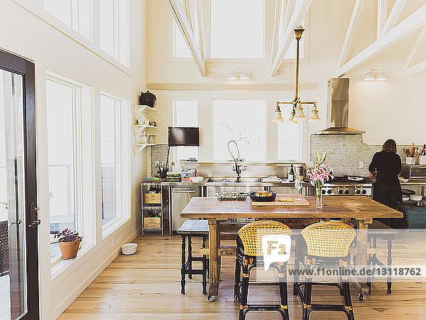 Rückansicht einer Frau  die zu Hause in der Küche arbeitet