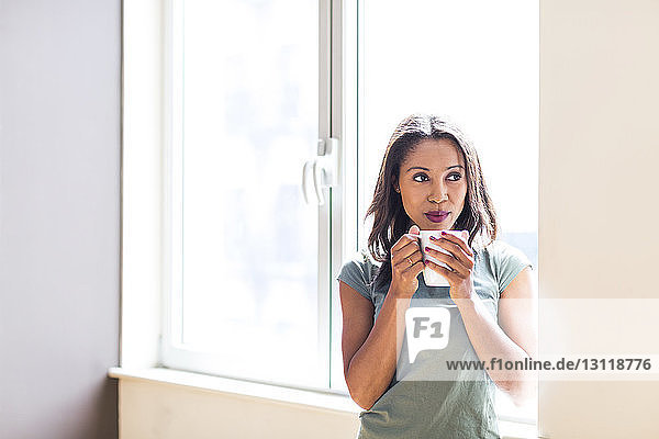 Thoughtful woman having coffee while standing against window at home